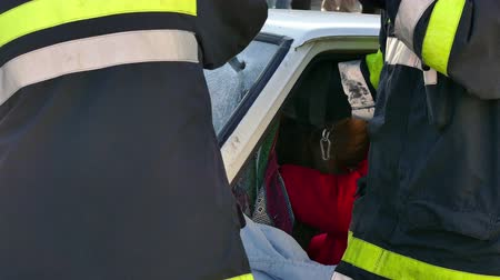 first person : Zrenjanin ; Serbia ; 22.11.2017.  Firefighters rescuer team breaks car glass to save injured driver-demonstration exercise.
