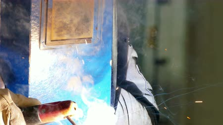 welding helmet : Metallurgy and Welding at the Factory ; Worker welder performs arc-welding process of metal structures