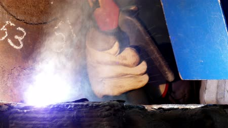 сварщик : Using a Welding Mask ; Worker welder performs arc-welding process of metal structures