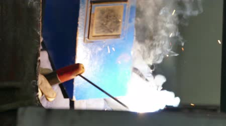 welding helmet : Sparks During Welding Process ; Worker welder performs arc-welding process of metal structures