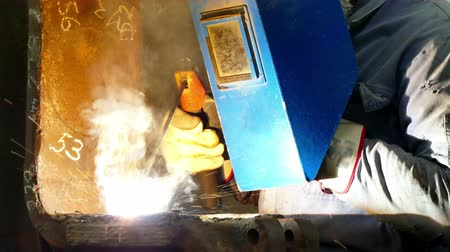 welding helmet : Worker with Welding Mask ; Worker welder performs arc-welding process of metal structures Stock Footage