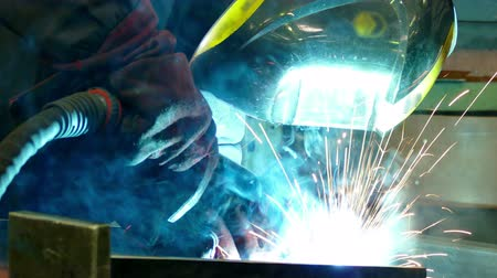 welding helmet : Welder Worker Performs Jump Welding  Worker welder performs arc-welding process of metal structures