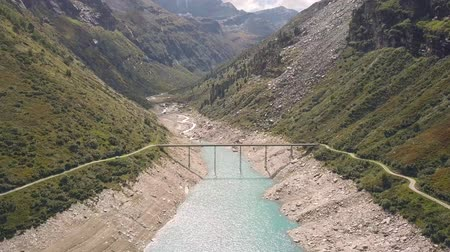 valais : Drone flight over a reservoir with a metal bridge Stock Footage