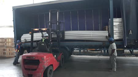 Red Fork Lift Loading Roud Duct Pipes In Blue Truck - Front Angle
