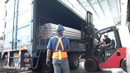 Red Fork Lift Loading Roud Duct Pipes In Blue Truck