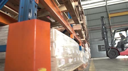 Red Fork Lift Taking Out Product From Shelf In Warehouse - Slider - Left to Right