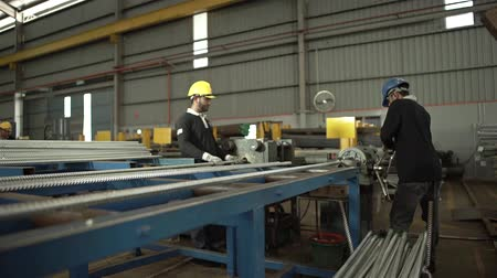 construction crane : Two Workers Working On A Machine Cutting Silver Pipes - Slider - Towards Stock Footage