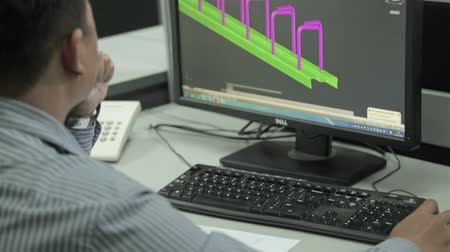 Man In Strip Shirt Working On Autocad On Engineering Design In Office - Over The Shoulder - Tilt Stock mozgókép