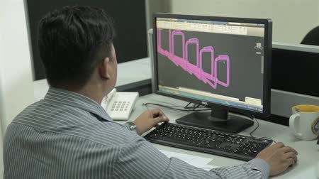 Man In Strip Shirt Working On Autocad On Engineering Design In Office - Over The Shoulder Stock mozgókép