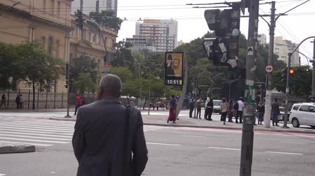 A Black Man With A Bag Crossing The Main Road