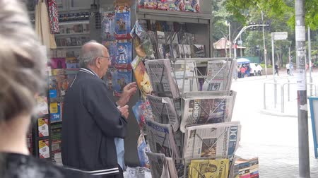 An Old Men Picking A New Paper From A Street Shop