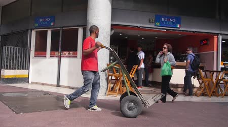 busking : Man Wearing Red Shirt Pushing A Trolley