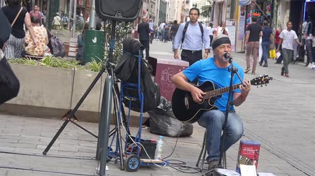 Old Man In Blue Shirt Busking In City Streets - Movimento - Da sinistra a destra Filmati Stock
