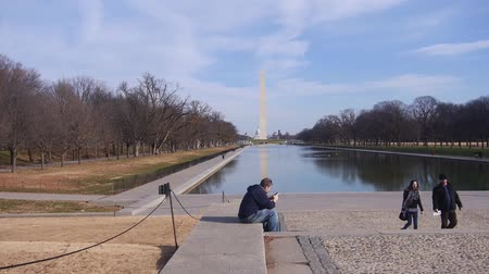 dc : Man Sitting With Phone Near People Walking, Water Source And Monument - Static