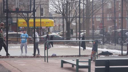 bronx : Men Playing Basketball Behind Fence Near Child - Static