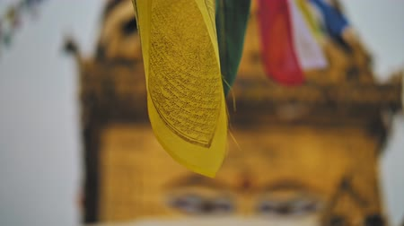 pináculo : Flags sways, blurred Buddhas eyes on golden stupa in Swayambhunath temple