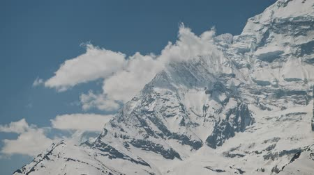 greatness : Close view on harsh frozen snow face of Annapurna II ridge with clouds, Nepal