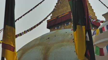 nepal : Insightful Buddhas eyes look from golden pinnacle of Boudhanath stupa, Kathmandu Stock Footage