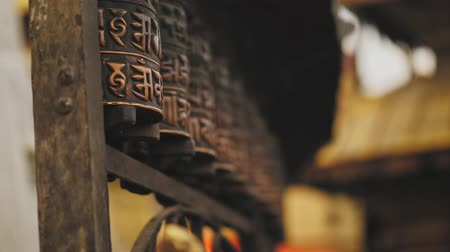 nepal : Buddhist polished carved rithual wheels spin at Swayambhunath temple, hand touch