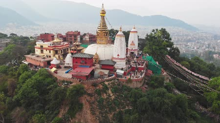 outlook : Aerial panorama. Swayambhunath temple on green hill. Kathmandu in smog