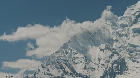 himalája : White clouds crawl over enormous snow ridge of Annapurna II mountain, Nepal Stock mozgókép