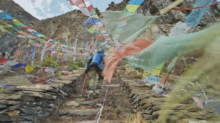 nepal : Tourist move upstairs among coloured prayer flags hung at Milarepa cave, Nepal Stock Footage