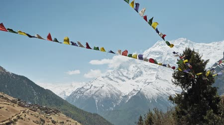 nepal : Prayer flags sway in wind, Annapurna II snow face nearby Ghyaru village, Nepal Stock Footage