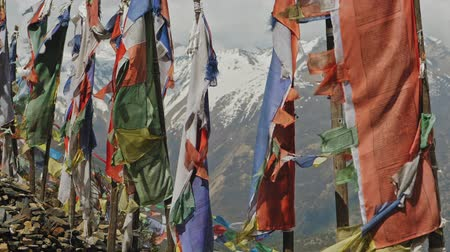 nepal : Colorful buddhist prayer flags on flagpoles sway over harsh snow mountain, Nepal Stock Footage
