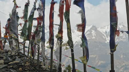 nepal : Coloured prayer flags on poles flap against severe snow mountains, Nepal Stock Footage