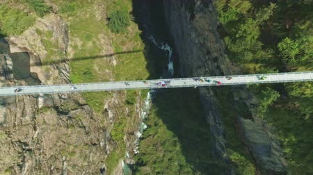 nepal : Tourists crossing narrow suspension bridge above deep river gorge