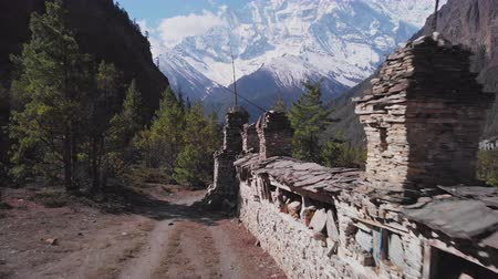 nepal : Trekking road near Mani wall lead through forest to snowy Annapurna II mountain