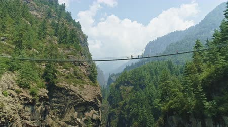 nepal : Panorama, travelers cross suspension bridge above deep mountain gorge, Nepal Stock Footage