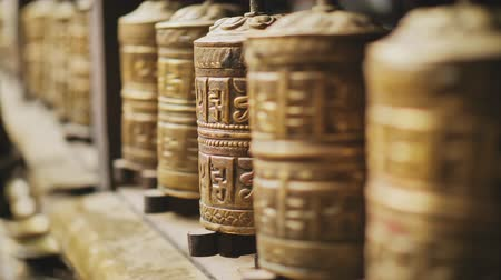 nepal : Pilgrim hand rotate row of golden metal prayer wheels, ritual circular spinning
