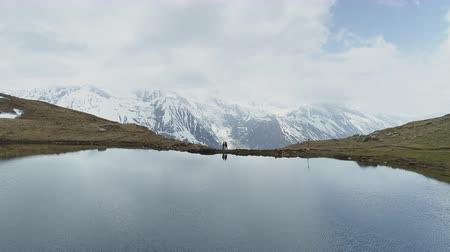 nepal : Two people stand at highland lake against snow cloudy Annapurna mountain, Nepal