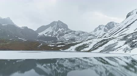 frozen lake : Sliding above mirror Ice Lake, snowy gloomy peaks reflect on smooth water, Nepal Stock Footage