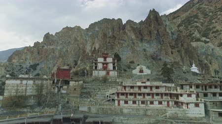 gompa : Aerial flight at empty windy Braga monastery nesting under crest cliffs, Nepal Stock Footage