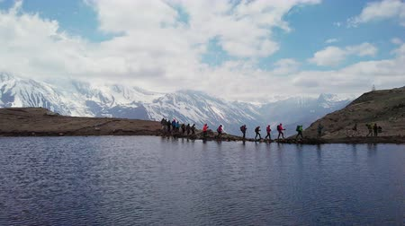 conquest : Trekking over lake, tourists at snowy mountains, sky reflection in water, Nepal