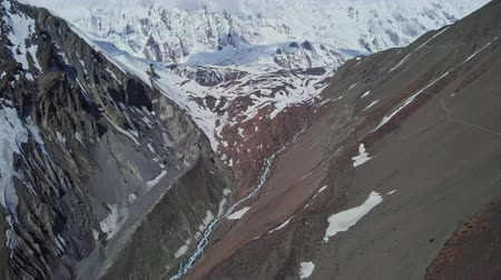 nepal : Atmospheric panoramic fly above river gorge near snowy mountain of Tilicho Peak