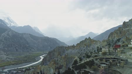 elvonult : Misty spacious river valley panorama, Braga monastery near crests cliffs, Nepal Stock mozgókép