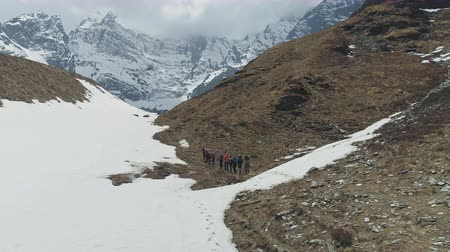 conquest : Tourists trekking over rocky slope, expedition to snowy Annapurna III mountain