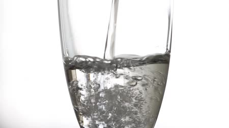 Pouring water with a glass pitcher in a transparent glass with white isolated background