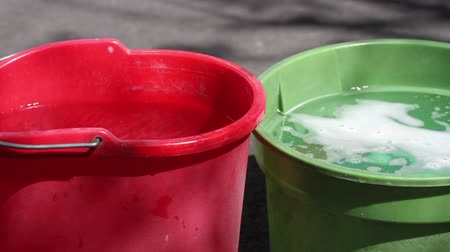 gąbka : Plastic household buckets in red and green with water and reflections