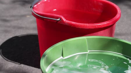 Plastic household buckets in red and green with water and reflections