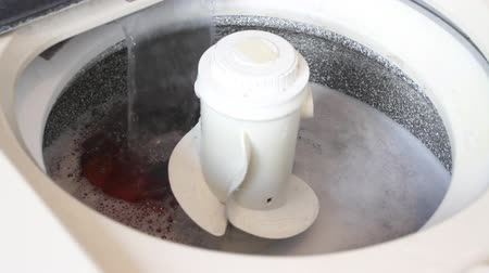 Wash machine spinning with clothes, water and soap