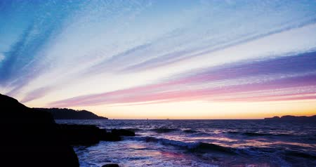 Beautiful Sunset at San Francisco Bay with colored clouds and sky and waves clashing in the rocks Wideo