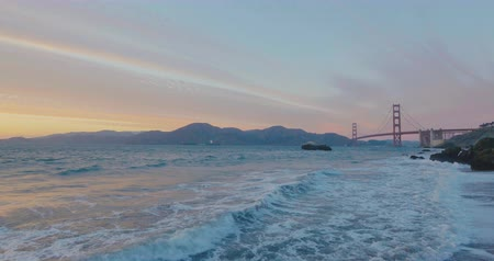 Beautiful sunset at the golden gate bridge in san francisco from baker beach view. Waves clashing at the clifs.  Big ship corssing at the distance Wideo