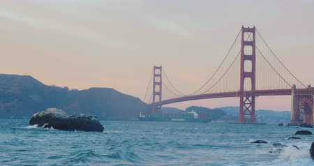 piekarz : Beautiful sunset at the golden gate bridge in san francisco from baker beach view. Waves clashing at the clifs.  Big ship corssing at the distance Wideo