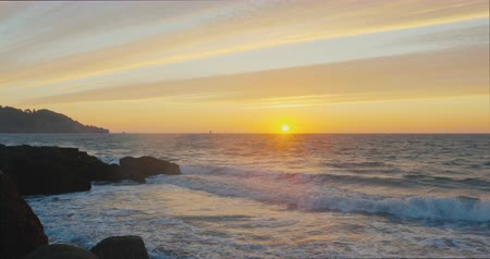 řek : Beautiful Sunset at San Francisco Bay with colored clouds and sky and waves clashing in the rocks Dostupné videozáznamy