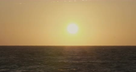 Sunset with a big yellow sun hiding at the distance by the sea with waves and sky Wideo