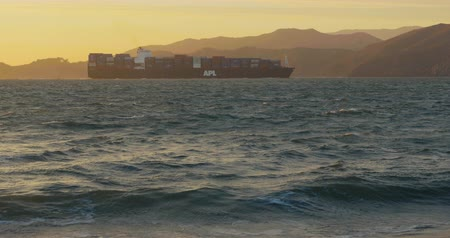 A big cargo ship with containers is slowly entering the port at san francisco by with the sun setting Wideo
